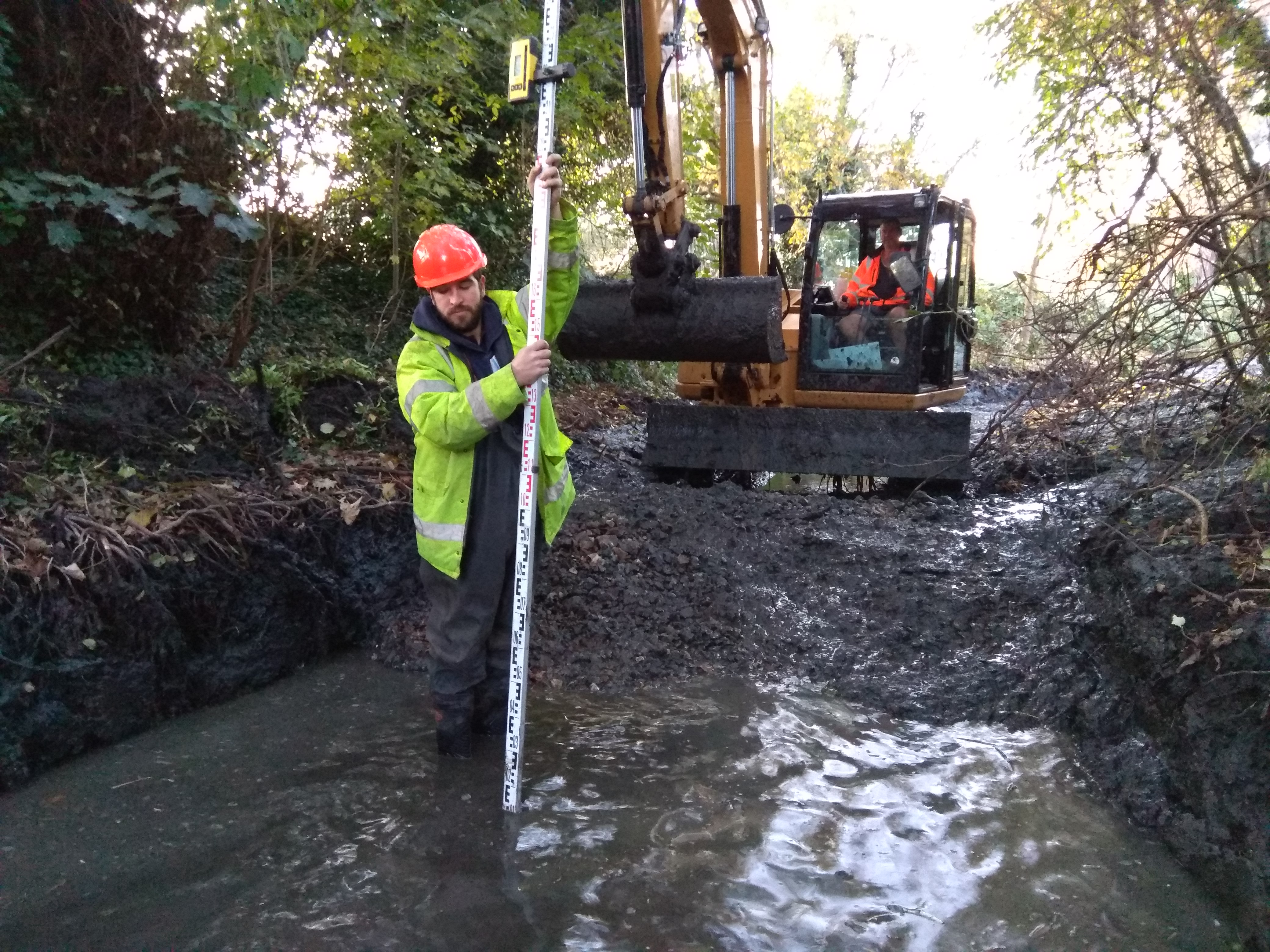 Miguel using the laser level to instruct Neville how deep to regrade the river bed